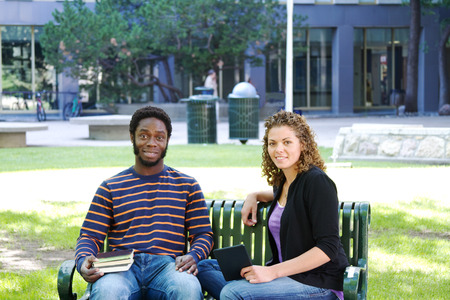 Two students visiting on bench on university campus photo