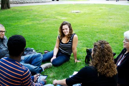Friends visiting outside on grass 版權商用圖片