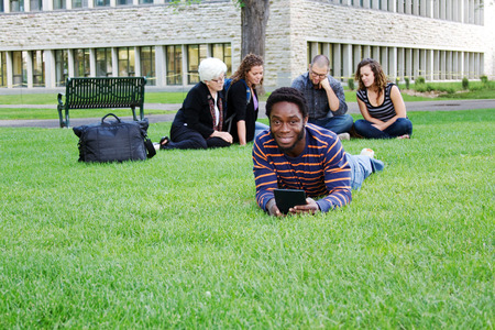 Student on grass with tablet, others in background