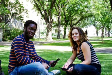 Two friends sitting on grass with tablets