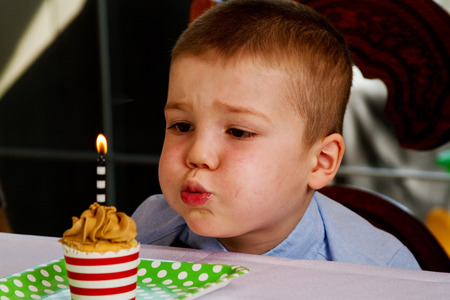 blow out: Bambino cercando di soffiare la candela su cupcake