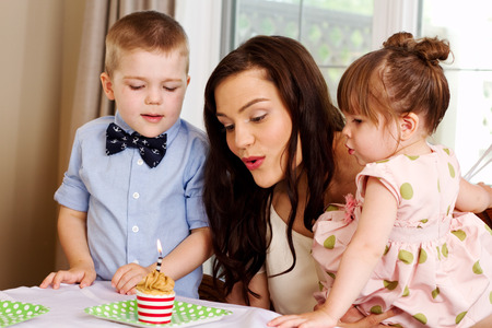 Mom and children blow out candle