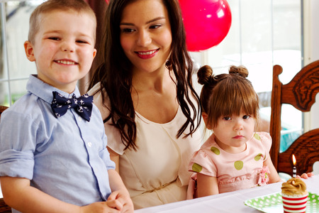 Mom sitting at table with children at birthday party Stock Photo