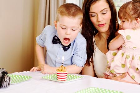 blow out: Giovane ragazzo pronto a spegnere la candela con la mamma e la sorella a guardare