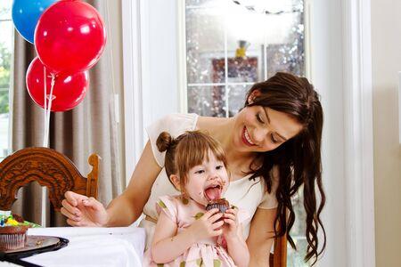 Toddler enjoying another cupcake at birthday party