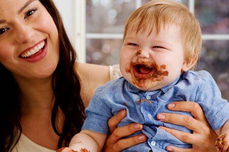 Mom and babe enjoying chocolate icing Stock Photo