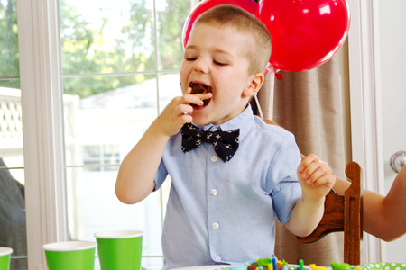 Small lad takes a large bite of cupcake Stock Photo