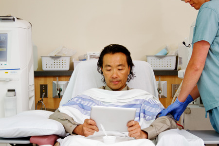 Asian patient looking at tablet during dialysis