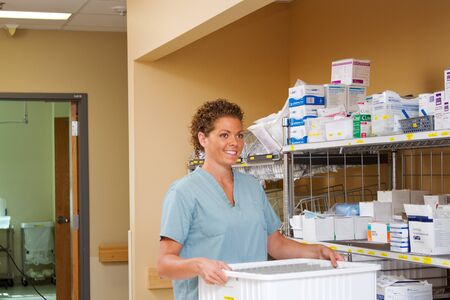 Nurse collecting supplies from a cart Stock Photo