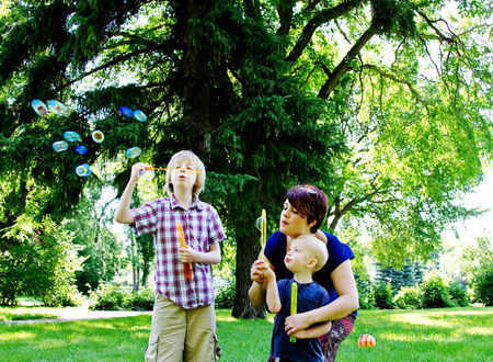 Boys blowing bubbles in park Stock Photo