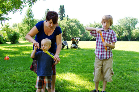 Mom instructing son on blowing bubbles at park