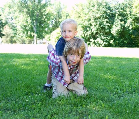 brothers playing: Dos hermanos que juegan en el parque en verano Foto de archivo