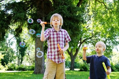 Little brother copying big brother blowing bubbles Stock Photo