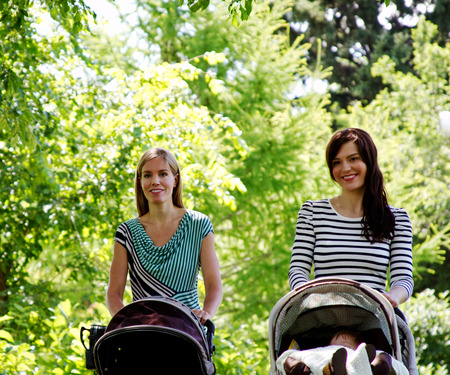 Two Moms pushing strollers and babies in park