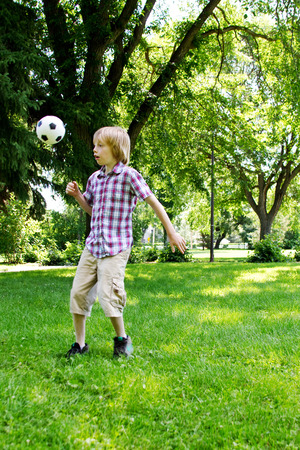 lad: Young lad playing with soccer ball in park