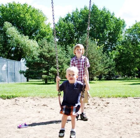 pushed: Youngster on swing being pushed by older boy Stock Photo