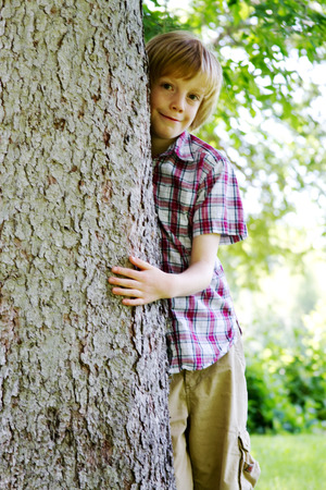 lad: Young lad hugging tree in park