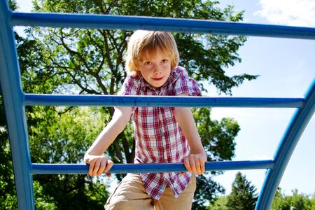 lad: Young lad climbing bars on playground Stock Photo
