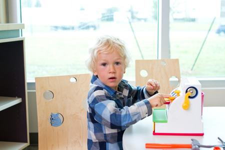 maquina registradora: Muchacho que juega con la caja registradora en la biblioteca