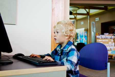 Small lad learning computer at the library Stock Photo