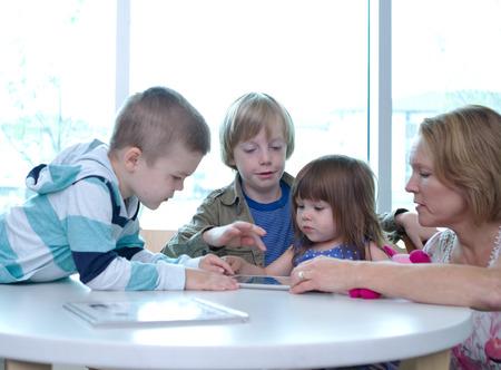 Three children and one adult on tablet Standard-Bild
