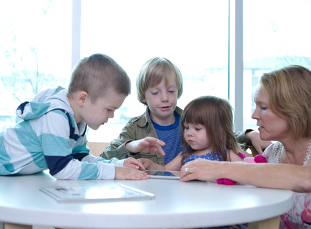 Three children and one adult on tablet Stock Photo