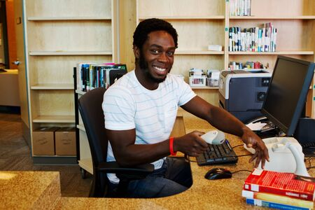 digital library: African librarian checking in books Stock Photo