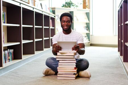 Young African man with books and tablet at library
