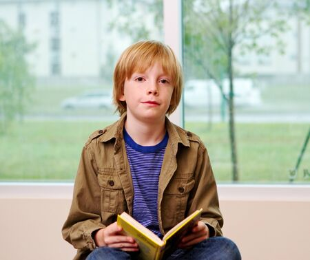 lad: Young lad reading book at library