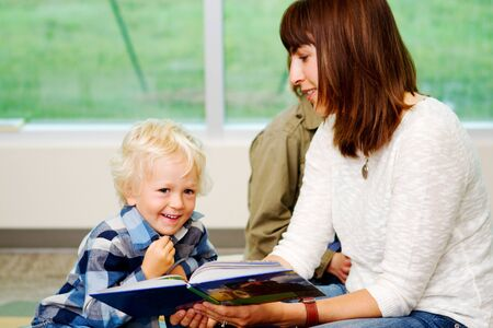 lad: Young lad enjoying story being read Stock Photo