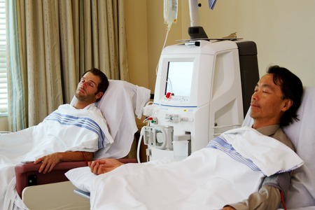 Two patients lying on stretchers in dialysis unit Stock Photo