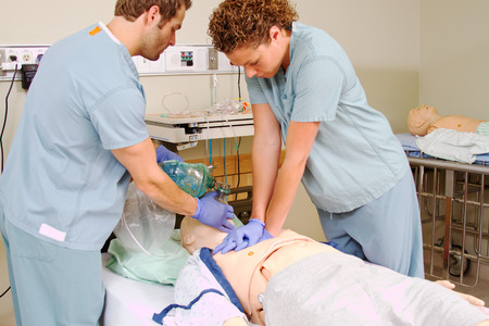 chest compression: Two medical staff practicing CPR on mannequin