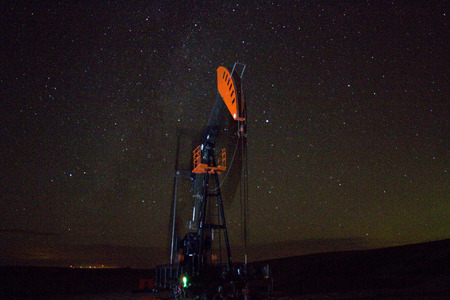 Starry sky with pump jack in foreground Фото со стока