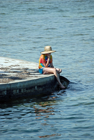 girl sitting down: Girl on Dock with Toes in Water Stock Photo