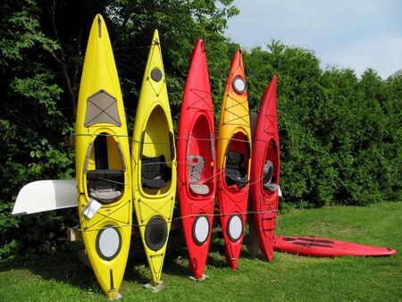 Row of colorful kayaks leaning against wooden rack Stock Photo