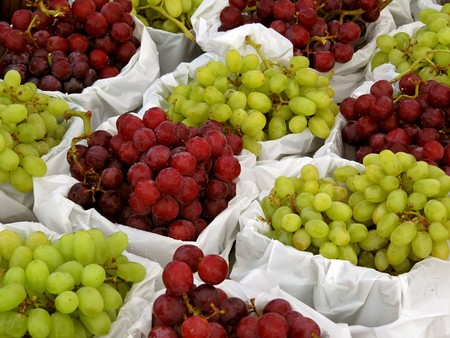 Baskets of green and purple grapes at a farmers market.         Stock Photo