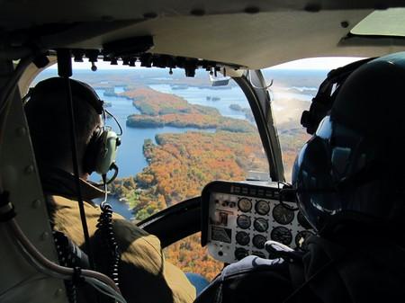 pilotos aviadores: Pilotos en la cabina del helic�ptero volando sobre los grandes lagos  Foto de archivo
