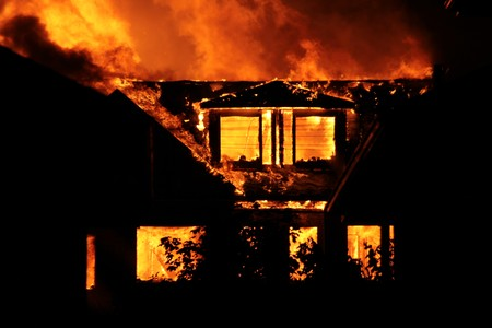 home destruction: House burning down at night