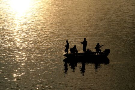 Fishing from the boat at sunset.