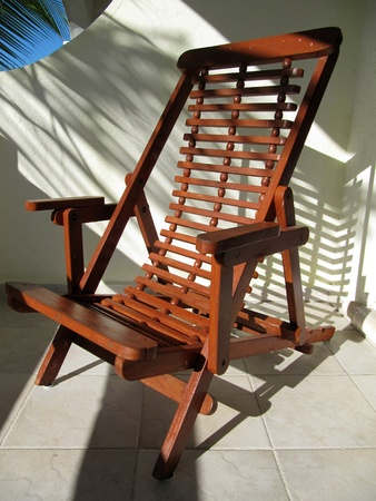 Empty wooden chair on a balcony facing the sun