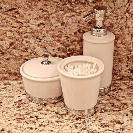 Ceramic bathroom accessories on top of a marble countertop Stock Photo