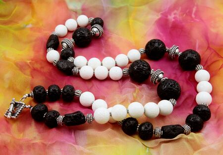 Closeup of a black and white lava stone necklace on a colorful background
