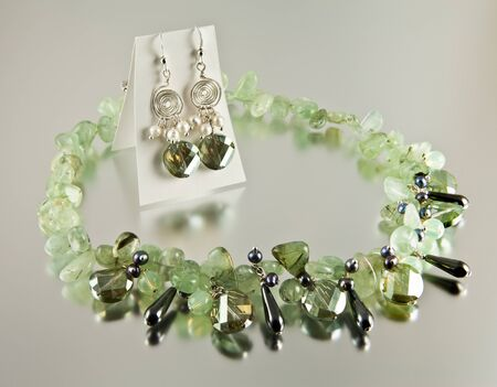 Green necklace and silver earings on silver background