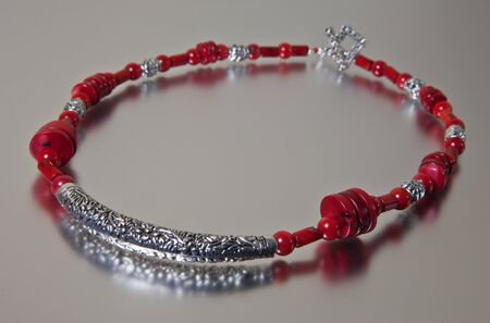 Red coral necklace on silver background