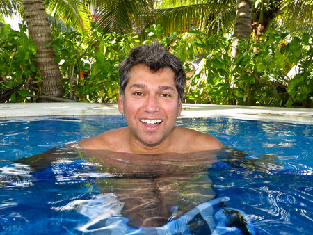 Young man relaxing in a pool in the tropics