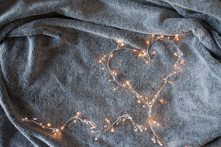 Garland with glowing lights in the background of a fluffy grey blanket, the comfort of home, the Christmas atmosphere.