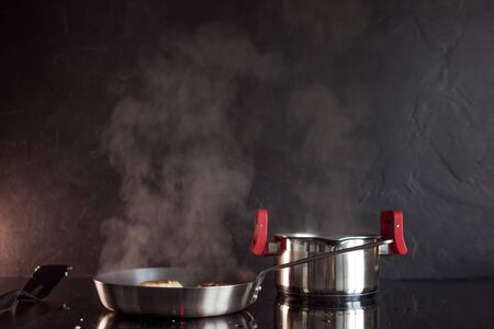 Frying pan and cooking pot on induction hob, steam rises. Black textured kitchen, cooking at home.