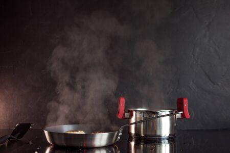 Padella e pentola di cottura sul piano di cottura a induzione, il vapore sale. Cucina strutturata nera, cucinante a casa. Archivio Fotografico
