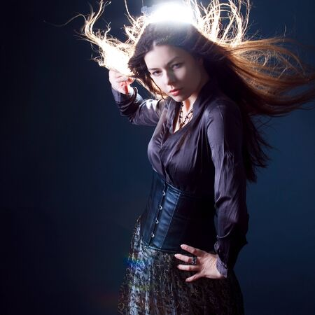Young attractive brunette woman in dark. Beautiful young witch image for Halloween. Girl with long flowing hair