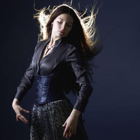 Jeune femme brune séduisante dans l'obscurité. Belle image de jeune sorcière pour Halloween. Fille aux longs cheveux flottants